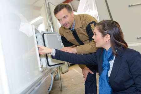 Woman looking at exterior cupboard on motorhome Stock Photo - 88216427
