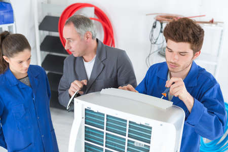 air-conditioning repairman with apprentices