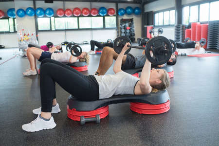group of people excercising with bars in gym