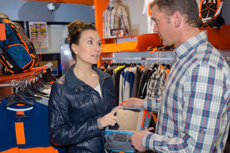 Woman talking sterly to man in clothes shop