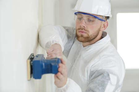 builder hand sanding interior wall for restoration Stok Fotoğraf