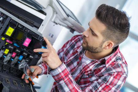 técnico masculino joven que repara la máquina digital de reparación