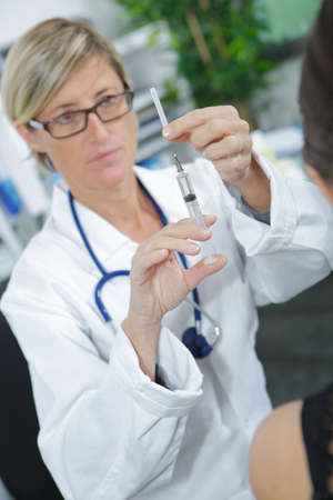 doctor injecting vaccine to the patient