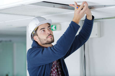 contractor unscrewing overhead ceiling panel Stock Photo