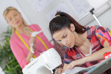 art processing: young woman sewing fabric on sewing machine