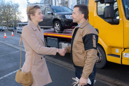 Woman shaking hands with man who has recovered her car Banque d'images