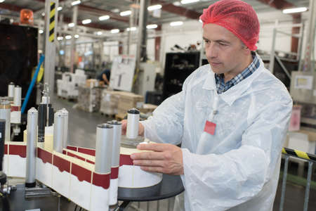 man in bottling plant working on labelling machine
