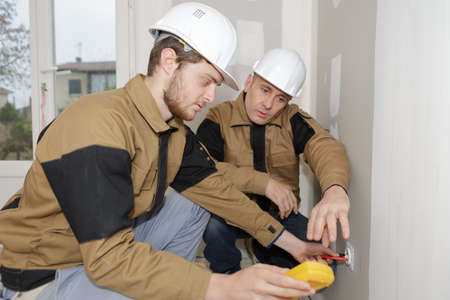 builders using a yellow multimeter to calibrate house
