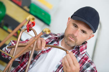 plumber using welding gas torch to solder copper pipes
