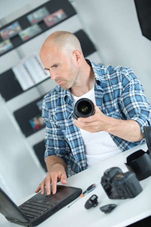 man holding camera lens and looking at laptop