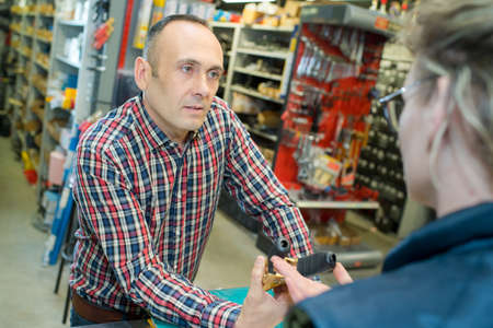 hardwarer store employee dealing with craftsman buyer
