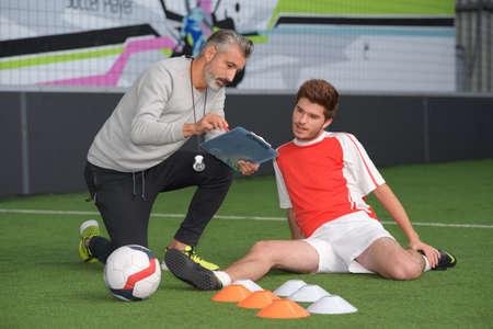 voetbalcoach geeft aanwijzingen aan speler
