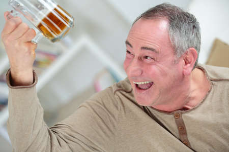 man holding a beer while laughing Stock Photo