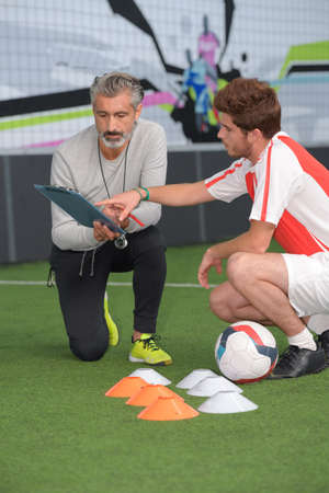 young male footballer in discussion with coach during training Stock Photo