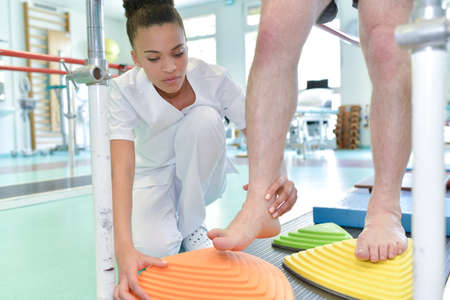 physiotherapist standing by patient on walking rehabilitation