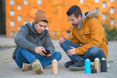 two young men doing street art graffiti Stock fotó