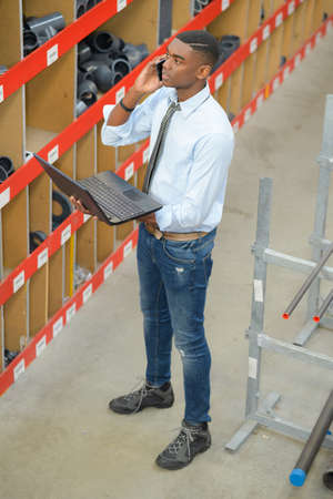 warehouse manager using telephone and laptop Stock Photo
