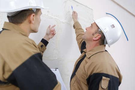 Workmen examining wall