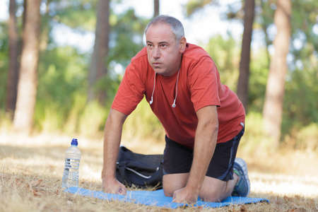 unfit: Middle aged man exercising on mat outdoors