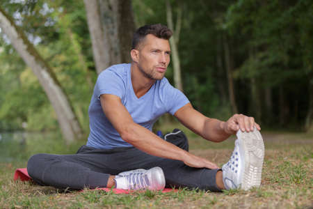 sportsman doing stretching exercises outdoors in a track Stock Photo