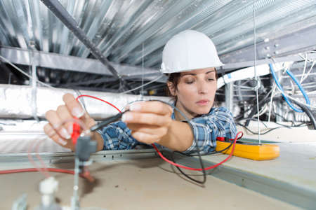female electrician installing of cables Stock Photo