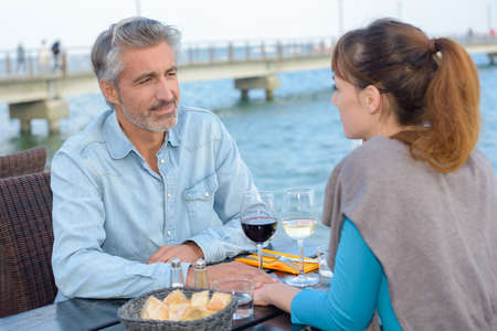 happy couple sitting at table in restaurant near by seaa Stock Photo