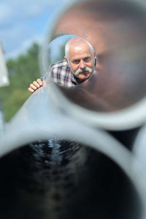 senior man looking through cement pipes in factory Stock Photo