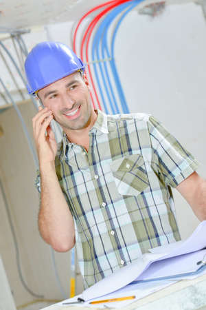 Builder on telephone, laughing Stock Photo