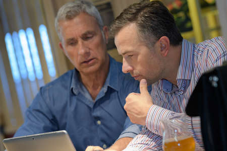 two middle aged businessman working late in office talking