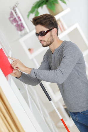 blind man reaching for a book Stock Photo