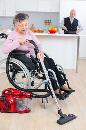 senior woman in wheelchair cleaning her house