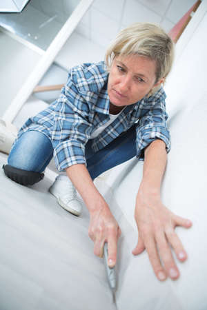 woman installing plinth paper Stock Photo