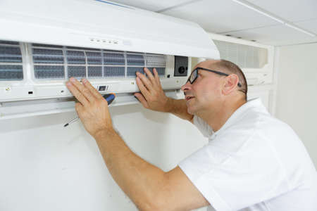 male technician checking air conditioner at home Stock Photo