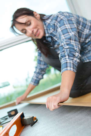 repairwoman laying laminate flooring at home Stock Photo