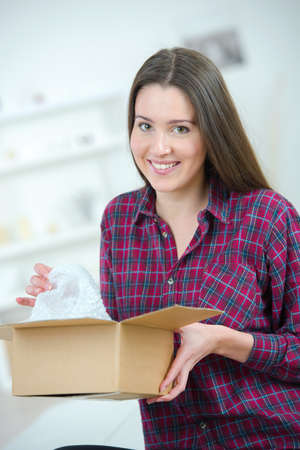 beautiful woman opening parcel at home Stock Photo