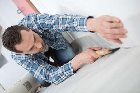 handyman installing carpet with cutter Stok Fotoğraf
