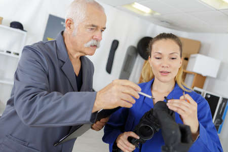 female apprentice learning about an engine Stock Photo