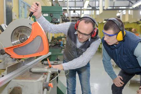 若い男の工場で丸鋸を示されています。 写真素材