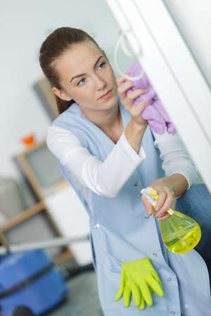 beautiful young woman cleaning windows at home Stock Photo