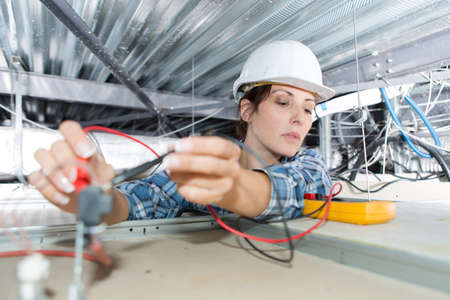female electrician checking voltage of ceiling cables