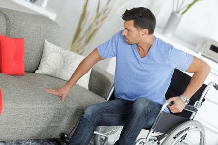 Man in wheelchair preparing to move himself onto sofa
