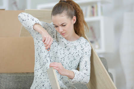 frustrated woman with self assembly furniture in kitchen