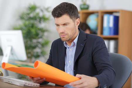 businessman opening roll of colored paper