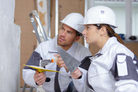 female and male plasterer at indoor wall renovation decoration Stock Photo