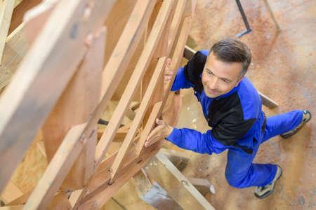 carpenter holding wood in workshop