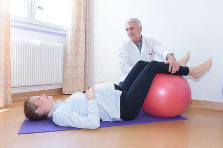 Doctor guiding pregnant womans legs on to aerobic ball Stock Photo