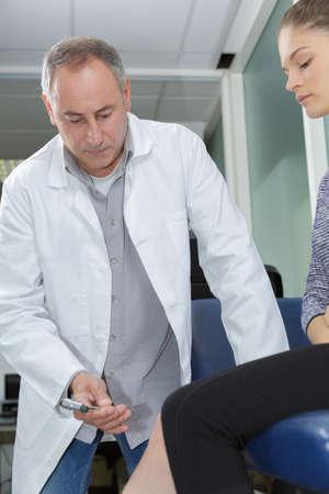 orthopedic surgeon examining the knee reflex