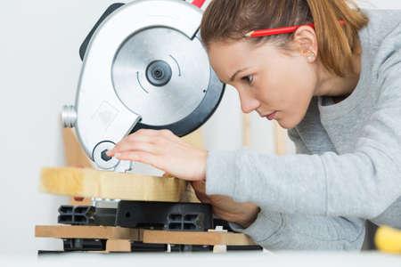 female carpenter is using a circular saw