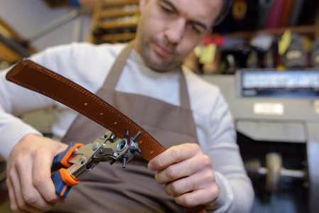 artisan belt worker making holes on the belt Stock Photo