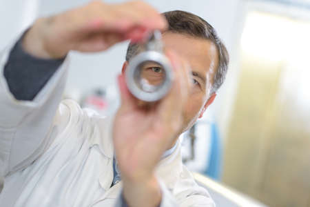ophthalmologist examines the eyes with handheld lense